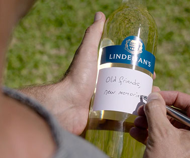 Man writes 'Old friends, new memories' on a label on a Lindeman's wine bottle