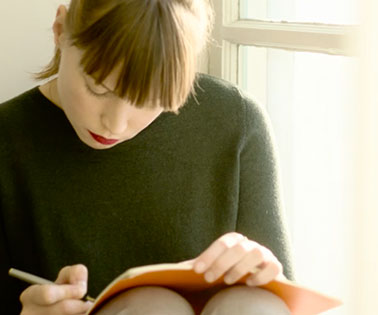 Girl sits on a window ledge writing in a notebook