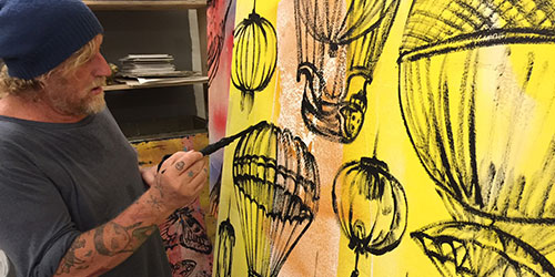 Artist David Bromley painting on a canvas